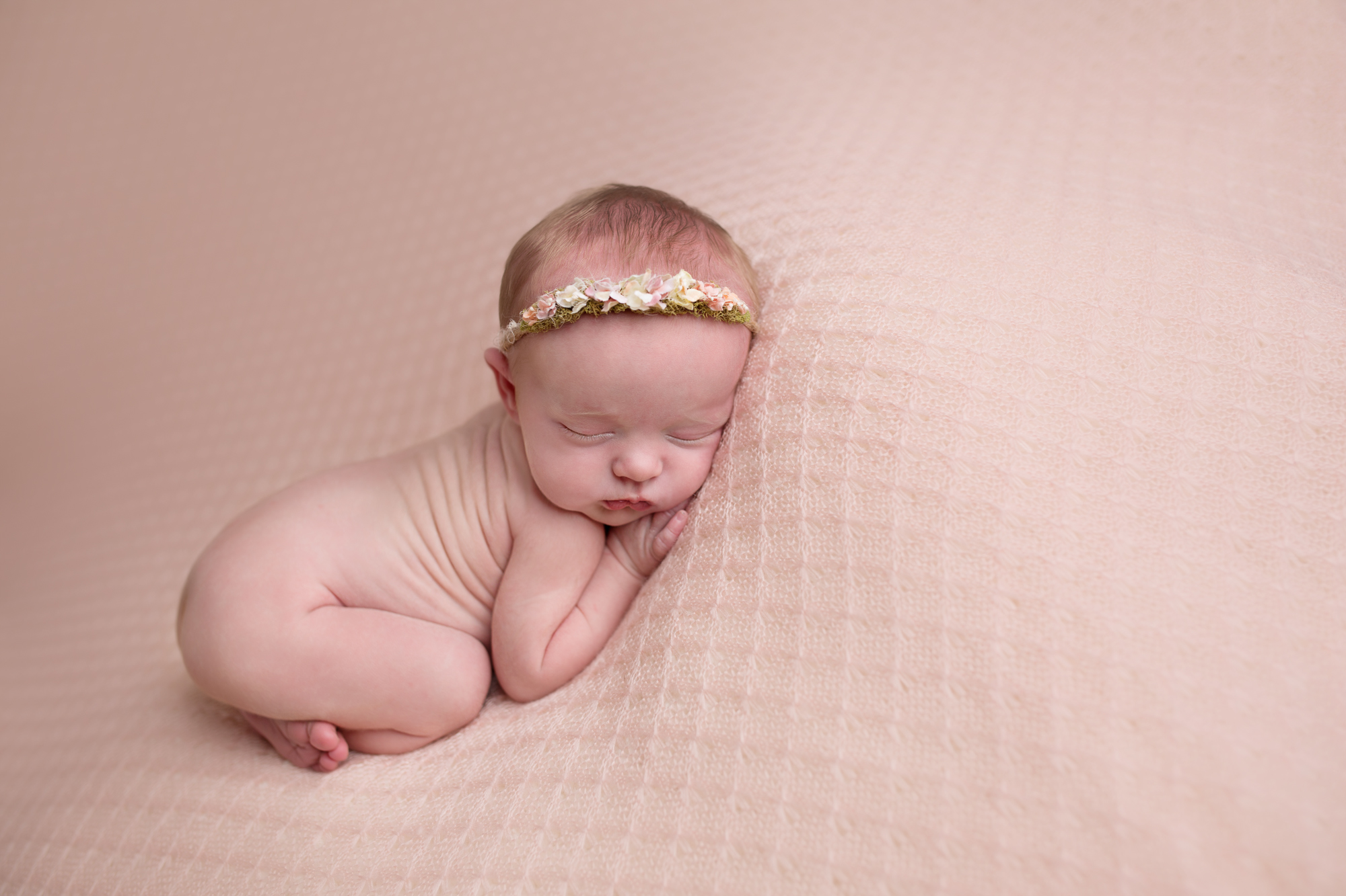 newborn baby girl on pink blanket