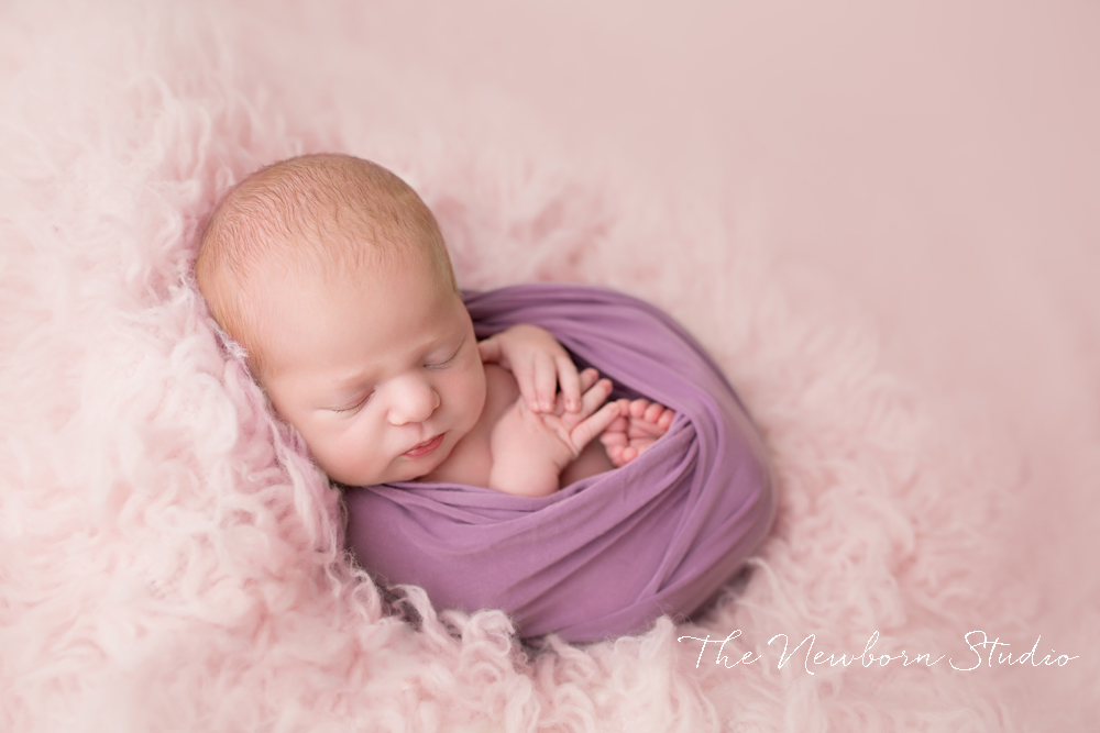 newborn baby girl wrapped purple and pink