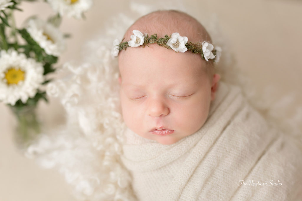 newborn baby girl wrapped flowers floral
