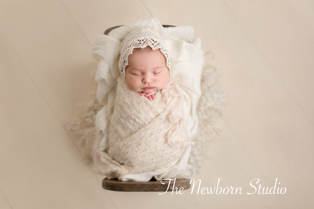 newborn baby girl photographed in studio bed