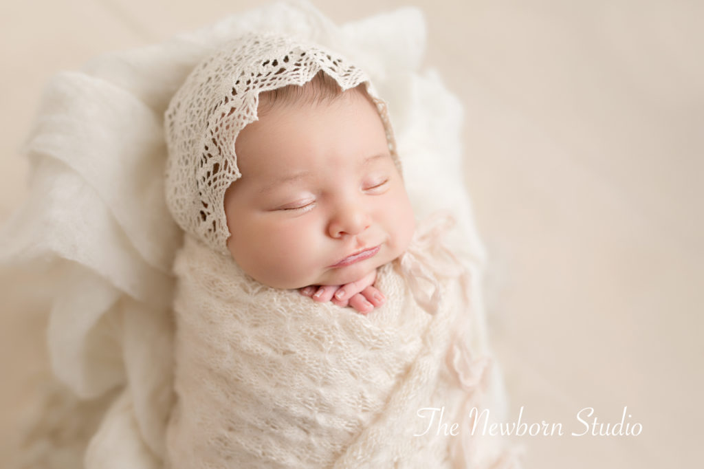 newborn baby girl wrapped smiling