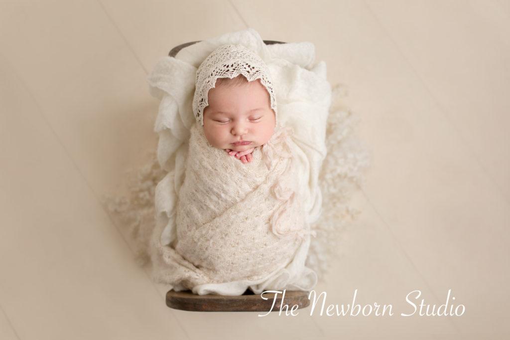 newborn baby girl photographed in studio bed