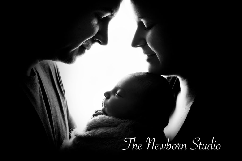 newborn baby girl parents backlit black and white