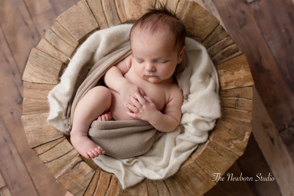baby boy curled up in timber bowl